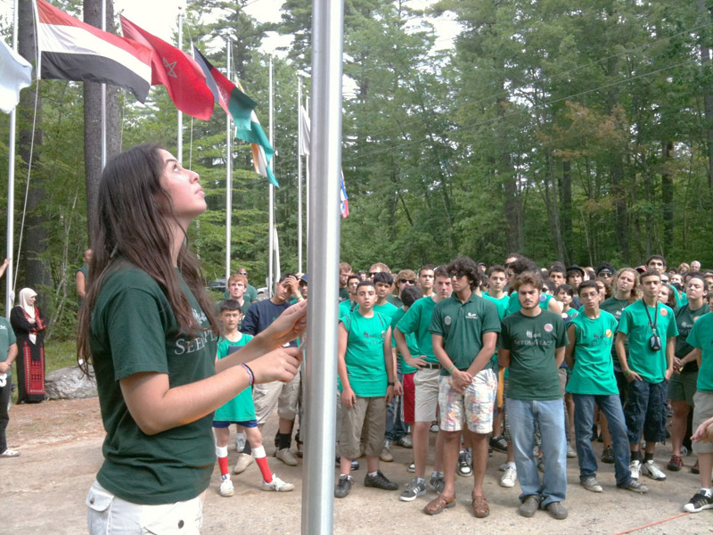 Mary-Kate Johnson, a counselor from New York, raises the Jordanian flag during opening ceremonies at the Seeds of Peace camp in Otisfield. There are 160 campers participating in this first session, which runs for 21 days.