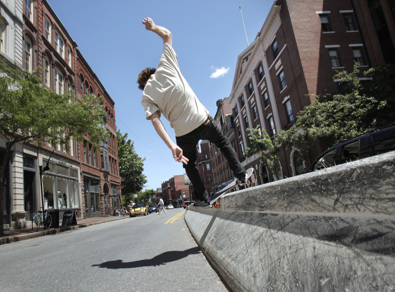 """Louis Reimensnyder grinds along the median divider on Middle Street in Portland on Wednesday. Later this summer, the city plans to build a $250,000 skate park at Dougherty Field near the I-295 overpass on Congress Street, but its design has generated some criticism from skateboarders. Reimensnyder says a skate park is desirable for the city. """"It does get people out of the streets,"""" he said."""