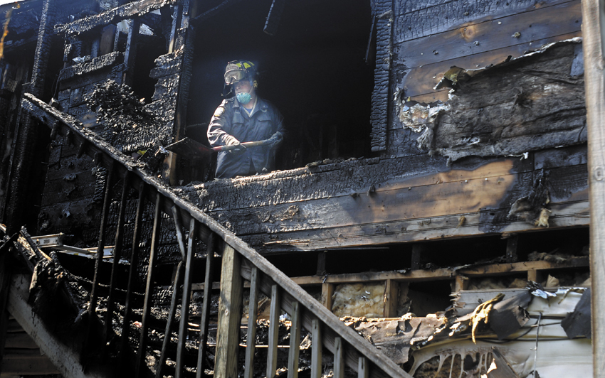 A state Fire Marshal's Office investigator shovels coals from a burned apartment Tuesday at 75 Second Street in Hallowell. An early-morning fire heavily damaged the multi-unit building. The cause of the fire, according to Hallowell Fire Chief Mike Grant, remains under investigation.