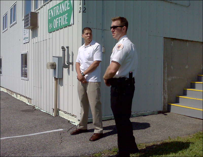 A pair of Secret Service agents wait by the entrance to the private hangar at the Hancock County-Bar Harbor Airport in Trenton that is expected to be used by the first family.
