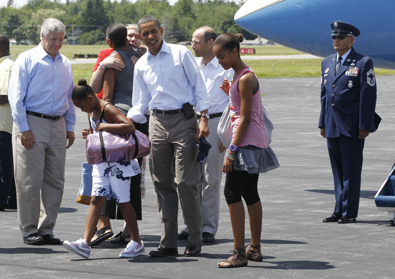 President Barack Obama with daughters Sasha and Malia after they were greeted by Maine Gov. John Baldacci, rear, center, Maine First Lady Karen Baldacci, hugging first lady Michelle Obama, rear, and Rep. Mike Michaud, D-Maine, at Hancock County Bar Harbor Airport in Trenton today.