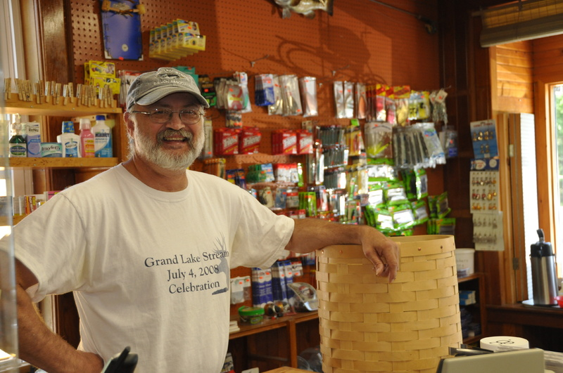 Kurt Cressey with a hand-woven pack basket at Pine Tree Store in Grand Lake Stream. He and his wife, Kathy, have run the store since April 1995.