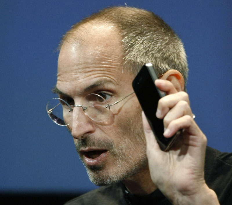 Apple CEO Steve Jobs holds up an iPhone 4 as he talks about how the company plans to address the phone's signal reception problem.