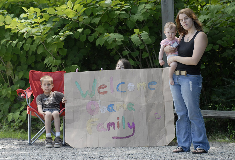 Melissa Abbott watches with hopes of seeing President Obama from her driveway along Route 3 in Bar Harbor along with her children, from left, Alec Zumwalt, 6, Evelyn Zumwalt, 8, holding the sign, and Keira Abbott, 1.