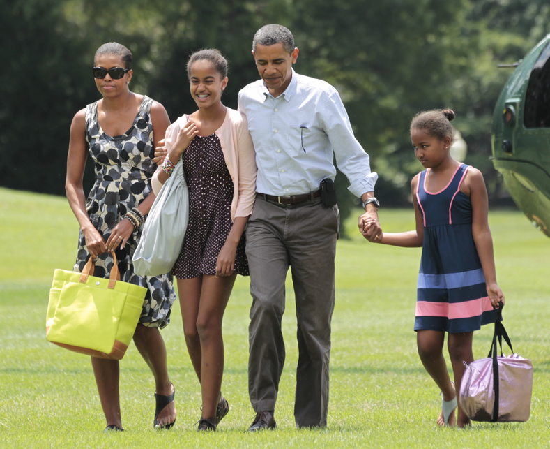 President Barack Obama, second right, first lady Michelle Obama, left, and their children Sasha and Malia Obama, second left, arrive on the South Lawn of the White House in Washington today after a weekend vacation on Mount Desert Island in Maine.