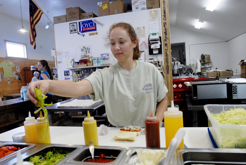 """Marietta Cox prepares a 4-inch """"cub sub"""" at Charlie Bennett's Store in Kennebunk. Locals have long made Bennett's a stop on the way to the beach, and tourists lucky enough to stumble upon it will find it a welcoming surprise."""