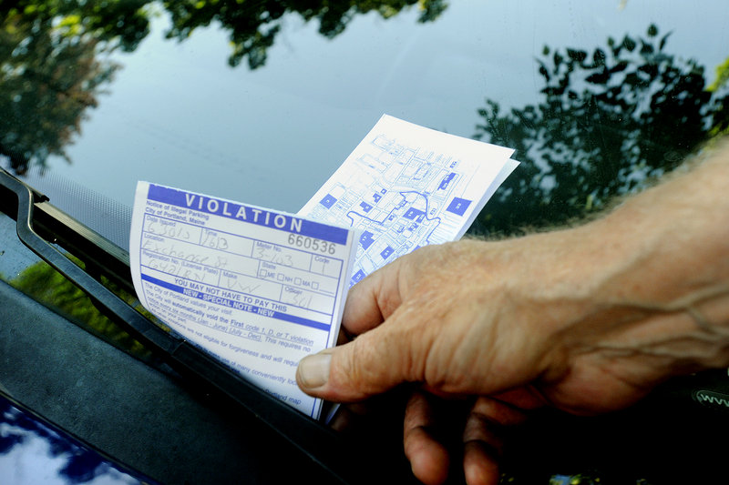 A Portland parking enforcement officer hands out a parking ticket Wednesday on Exchange Street. With the city struggling to balance its budget, starting today, no more minor parking tickets will be forgiven.