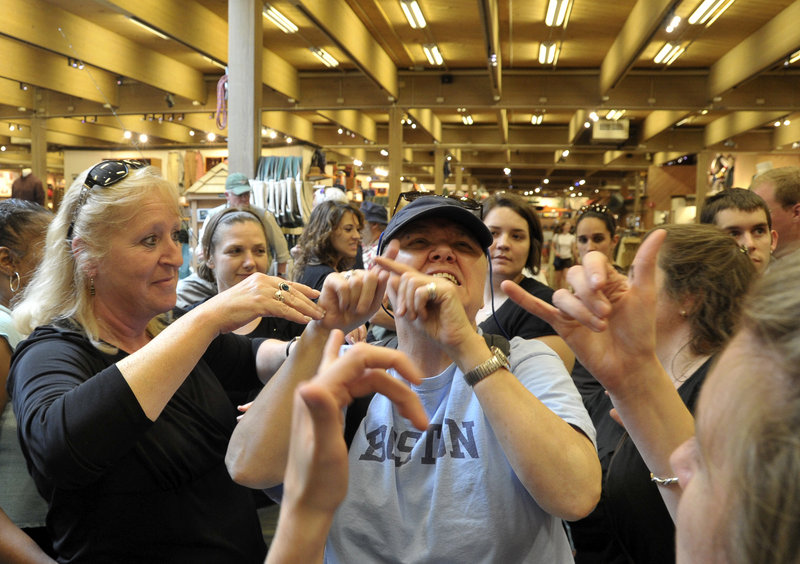 Jane Gammon, left, and others in an interpreting course describe the layout and merchandise at L.L. Bean in Freeport on Thursday for Ona Stewart, who is deaf and blind. They are using American Sign Language close enough for her to understand.