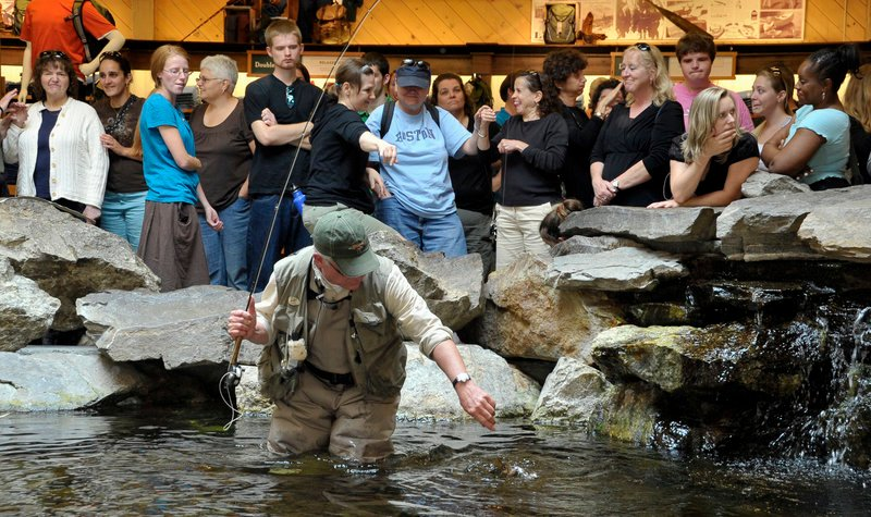 Estes demonstrates the catch-and-release technique in fly fishing for the interpreting program group at Bean's indoor trout pond.