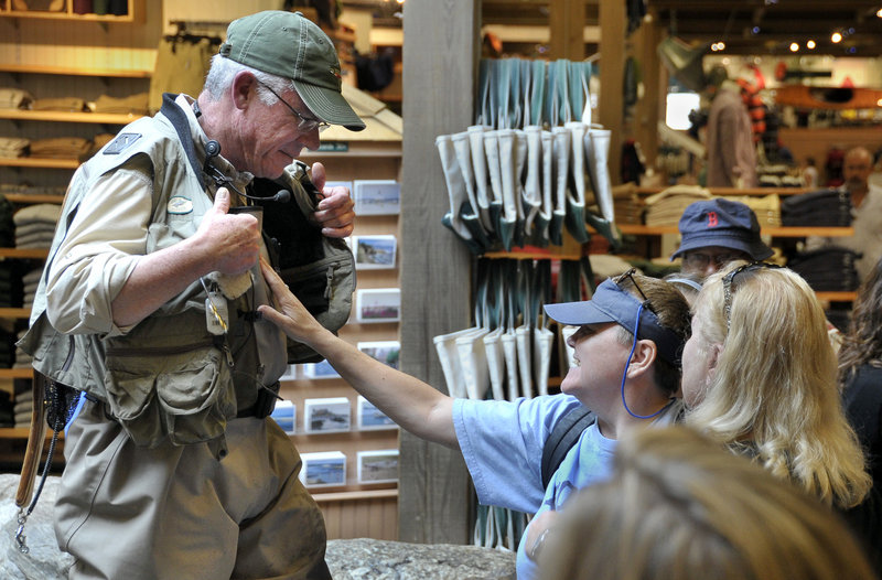 Ken Estes of L.L. Bean lets Ona Stewart feel his fishing outfit as part of a visit to the store by people who are blind and deaf and the students learning to interpret and support them.