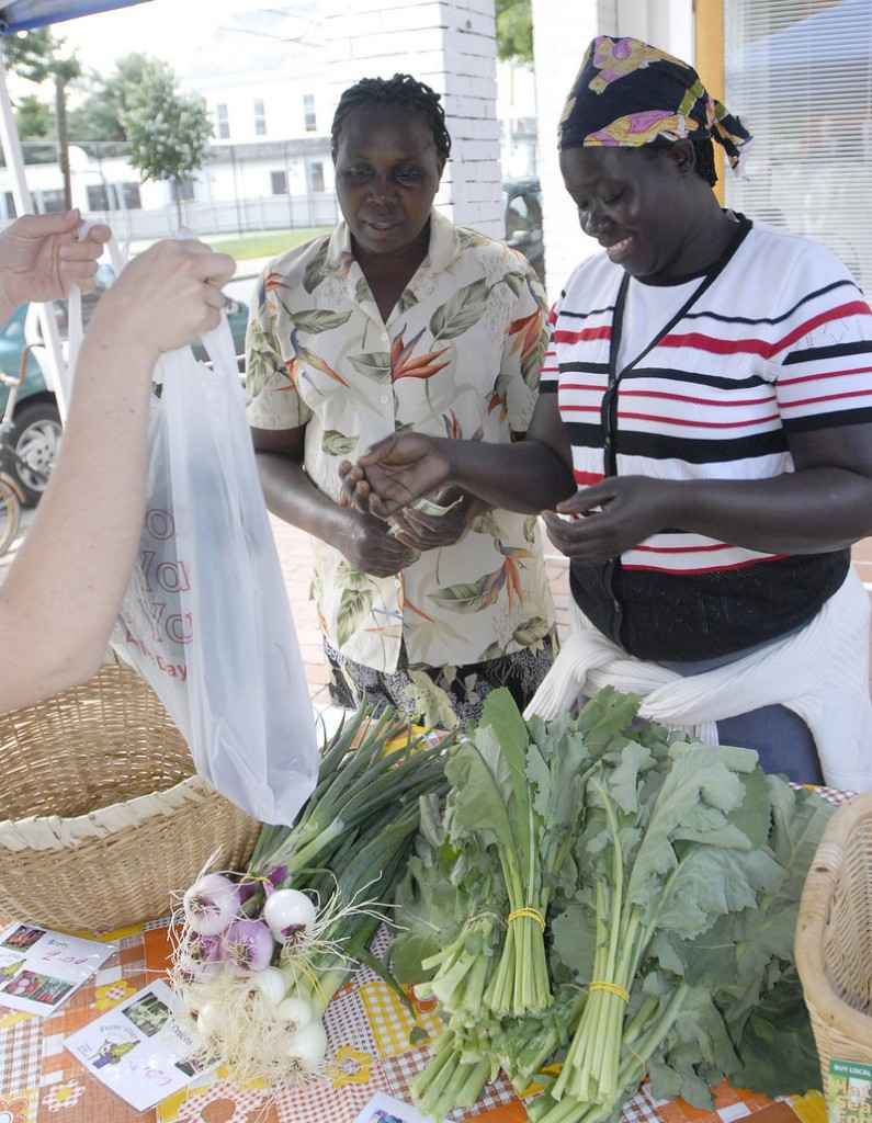"Christine Lokoware, left, and Santa John, both of Portland, sell vegetables at the new Brackett Street market in Portland on Thursday. Lokoware says she tries to keep her children eating fresh produce despite all of the soda and processed foods available in stores here. ""If you don't buy soda, they are not going to drink it,"" she said."