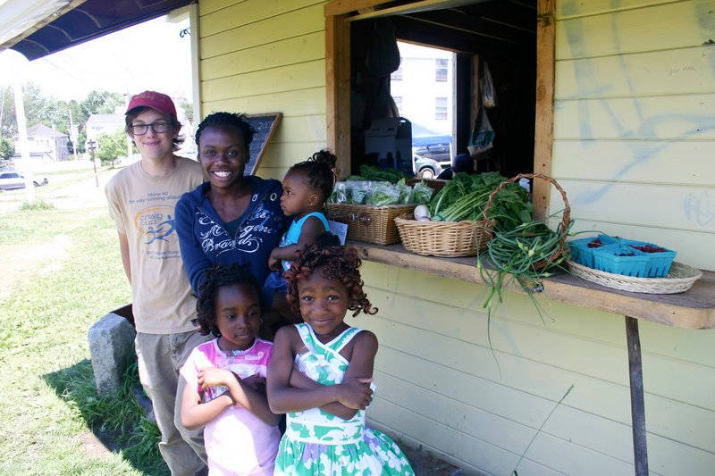 Tyler O'Brien and Mary Nyembo of the Youth Growers program are seen at the market with Nyembo's cousins Agnes, Dorcas and Bettina Bolese, who live in the neighborhood.