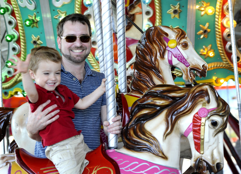 Two-year-old Sawyer Blake and his father, Sterling Blake, of Bath ride the merry-go-round at the 38th annual Bath Heritage Days on Saturday.