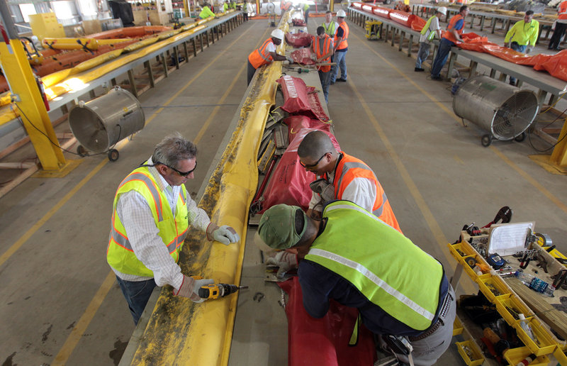 Workers at the Theodore Staging Area in Theodore, Ala., make repairs to damaged oil retention booms on Sunday. The BP leak is gushing up to 60,000 barrels of oil a day, according to government estimates.