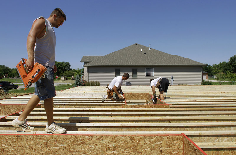 Construction workers Jeremy Jarrard, left, Ryan Turner and Joe Hubbell work on a new home in Springfield, Ill. The service sector grew more slowly in June, an industry group said.