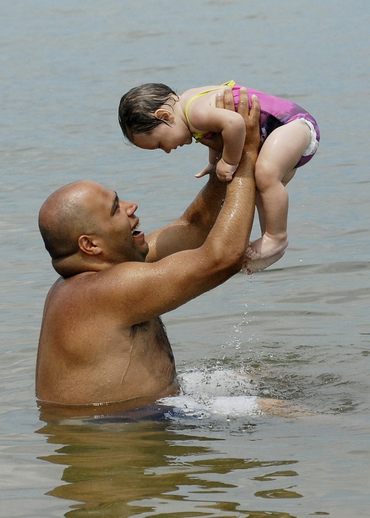 Eloy Figueroa of Portland cools off with 10-month-old Nevaeh Figueroa on Tuesday at East End Beach in Portland.