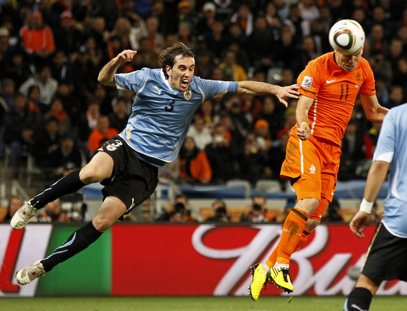Uruguay's Diego Godin, left, arrives too late to stop the Netherlands' Arjen Robben from scoring on a header to give the Netherlands a 3-1 lead Tuesday during a World Cup semifinal in Cape Town, South Africa.