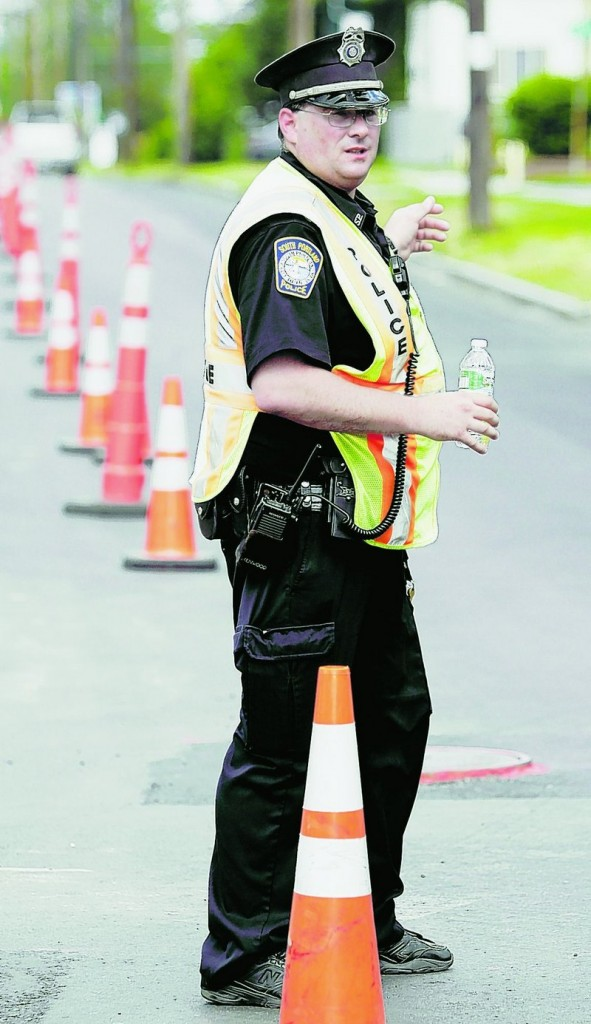 Officer Robert Libby directs traffic around a construction site on Broadway in South Portland on Tuesday.