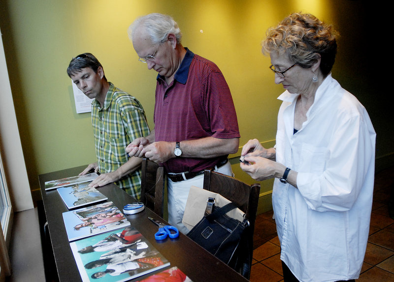 Photographer Gregory Rec of The Portland Press Herald/Maine Sunday Telegram, left, looks over photographs from his trip to Haiti, with Malcolm Rogers and Wendy Taylor, both of Konbit Sante, on Tuesday.
