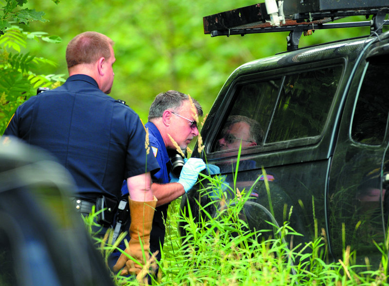 Officers look in the back of James F. Popkowski's pickup truck, which was found parked off Route 17 on Thursday.