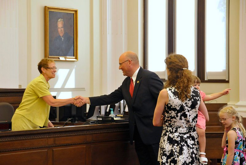 Noel C. March shakes hands with Linda Jacobson, clerk of the United States District Court, with his family at his side.
