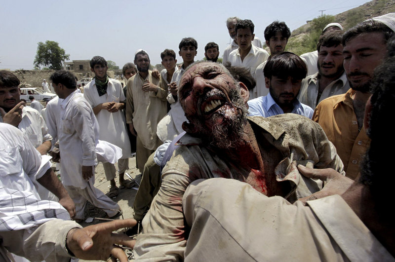 Pakistani villagers carry an injured person after a bombing in a Pakistani tribal area of Mohmand on Friday.