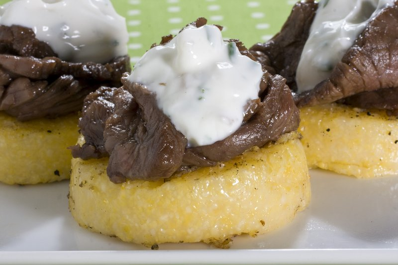 The Associated Press Thinly sliced and marinated sirloin is delicious served on top of polenta.