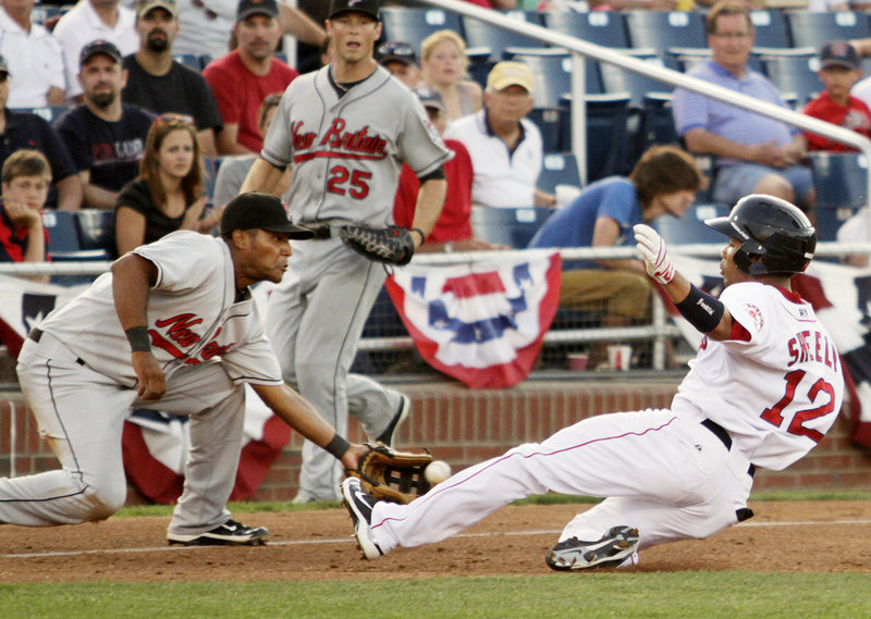 Matt Sheely of the Sea Dogs beats a throw to New Britain third baseman Juan Portes and slides in for a triple during the fourth inning of Portland's 7-5 victory Friday night at Hadlock Field. Sheely later scored after drawing an errant throw.