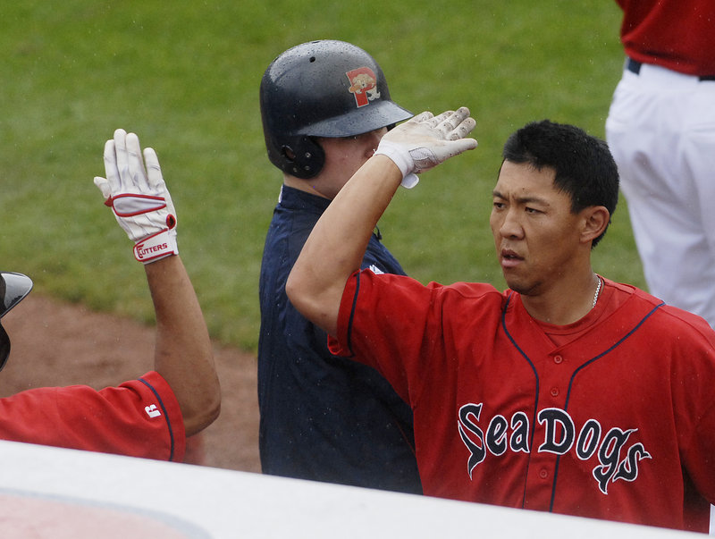 Sea Dogs third baseman Ray Chang is congratulated by a teammate after hitting a home run in the first inning Sunday against the New Britain Rock Cats. Anthony Rizzo also homered for the Sea Dogs in a 7-3 win.