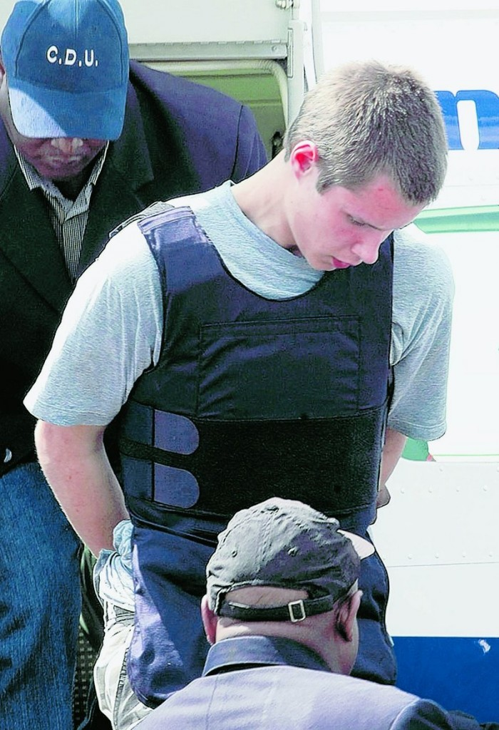 Colton Harris-Moore is escorted by police as he arrives in Nassau, Bahamas, following his arrest Sunday.
