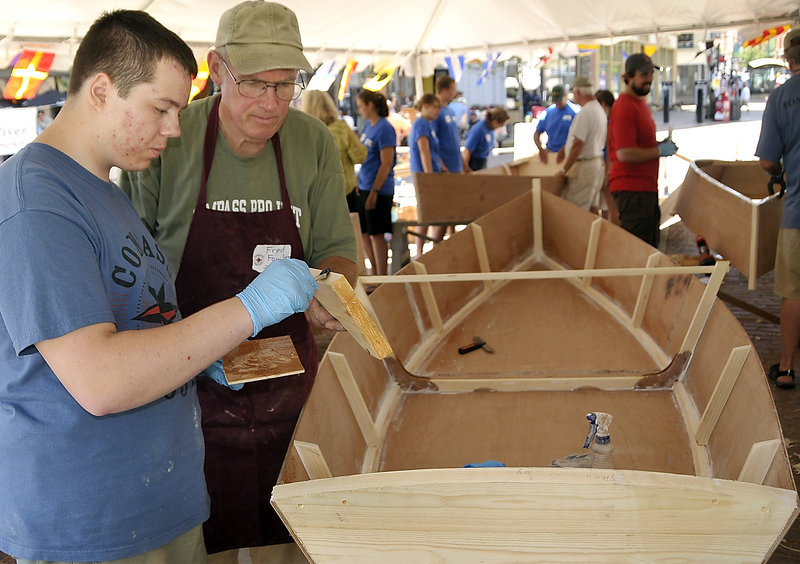 Billy Babin, left, gets help from instructor Fred Fowler as Babin applies glue to a part of a Bevins skiff he is building Monday. The Compass Project gives students from Greater Portland a chance to enjoy boat building and improve their confidence and work ethic.