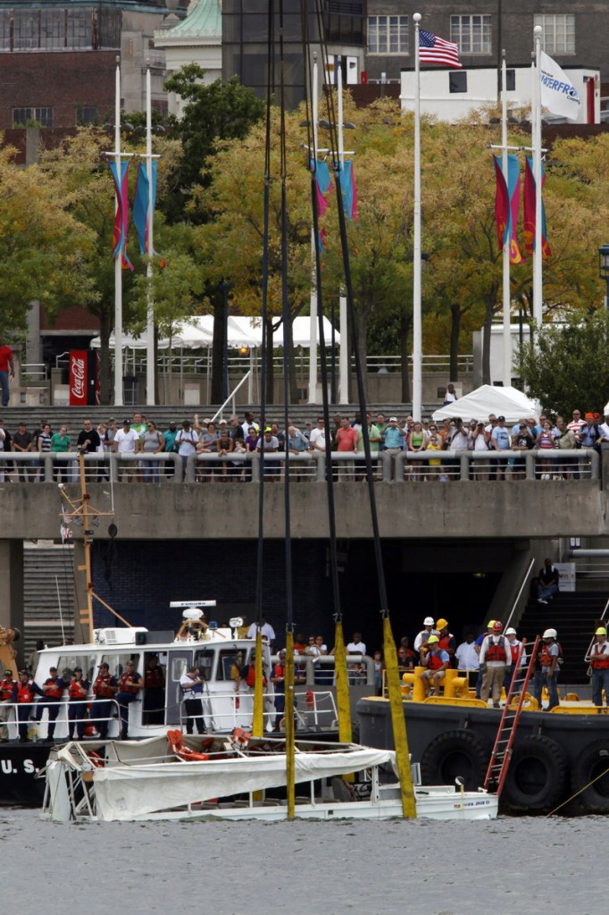 People watch as a duck boat is salvaged from the Delaware River in Philadelphia on Friday. Two people died when a barge struck it last week.
