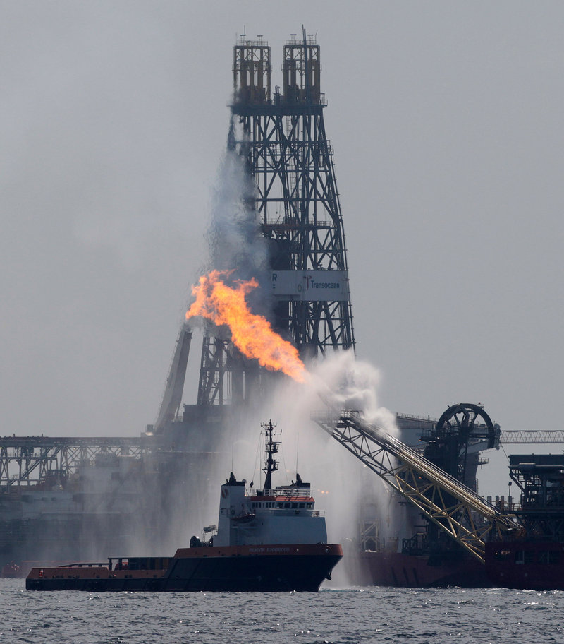 A work boat, left, operates near the oil-processing ship the Helix Producer, right, on Tuesday in the area of the Deepwater Horizon oil spill in the Gulf of Mexico.