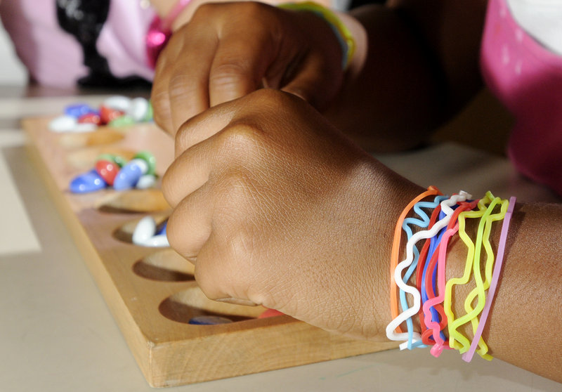 Dominique Hamilton wears her Silly Bandz while playing a game of Mancala. Popularity of the colorful rubber bands that retain specific shapes has exploded. Kids wear, trade and collect them.