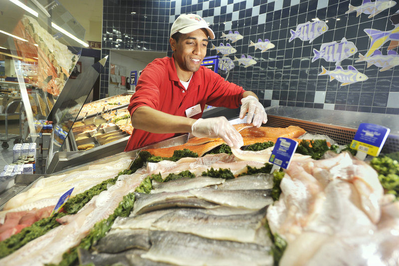 Assistant seafood manager Nabil Sibouih arranges fish fillets in a display case Thursday at Hannaford's Forest Avenue store.