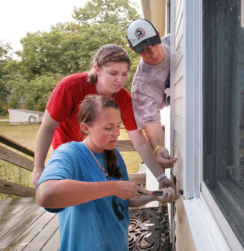 William Tryon, right, offers advice to Hannah Foster, left, and Kallie Hoinacki as the girls install a piece of siding at the Kennebunk home of Cathy McCollet on Wednesday. The three are participating in a program called workcampNE, which puts teenagers to work on home repairs at the houses of elderly and disabled people. Tryon is the crew leader of the group. The camp, which hosts teens from as far away as Illinois and Canada, is using Kennebunk Middle School as its base of operation.