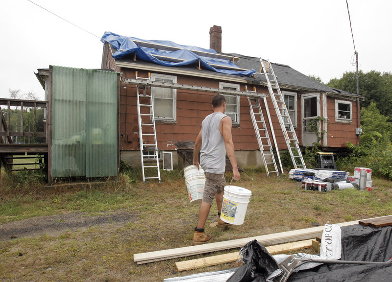 """Dan D'Amato of New York cleans up at the end of the work day Wednesday in Wells. """"This camp gives teens the opportunity to have a week of Christian fellowship, all the while helping the local community,"""" said Ken Therrien, a founder of workcampNE."""