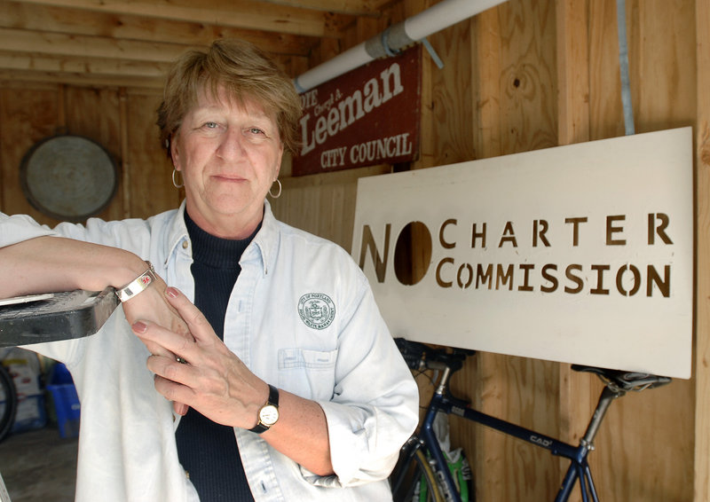City Councilor Cheryl Leeman shows off an old campaign sign in her Portland garage in 2008. Leeman opposes the Charter Commission's proposal for a full-time elected mayor.