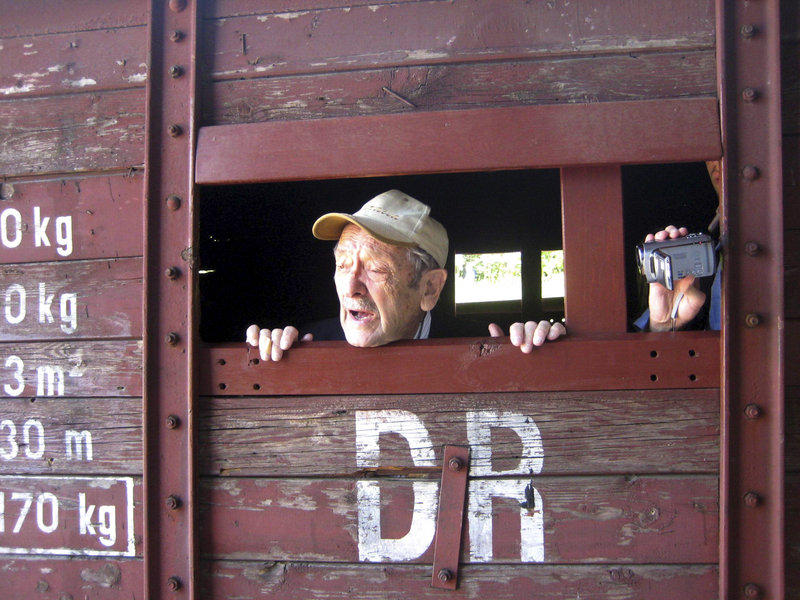 Adolek Kohn, 89, looks out the window of a train freight car that used to transport people to the Auschwitz death camp in Poland in this image taken during the making of a video clip that became controversial on the Internet.
