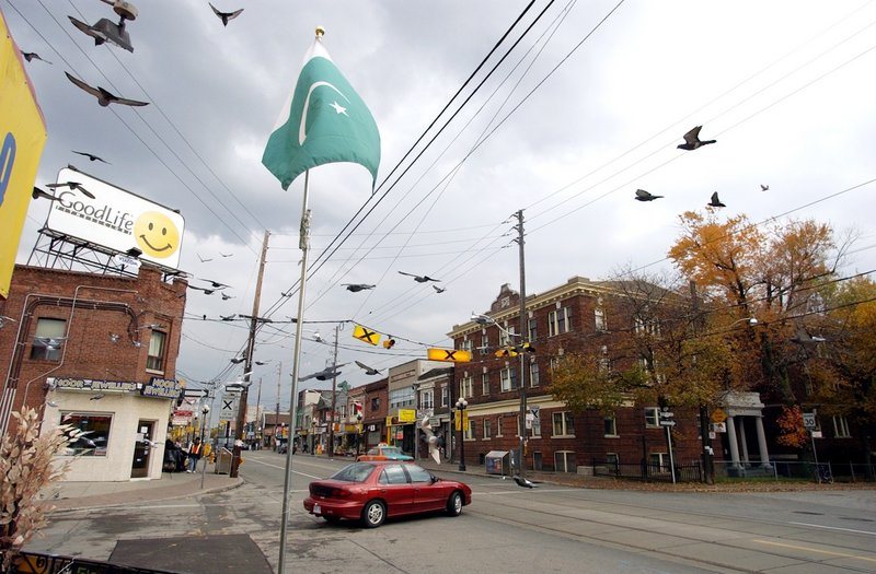 A Pakistani flag flies along a street in Toronto, where many South Asian immigrants have settled. Canada's immigration policy emphasizes opening the door to skilled professionals and other productive workers.