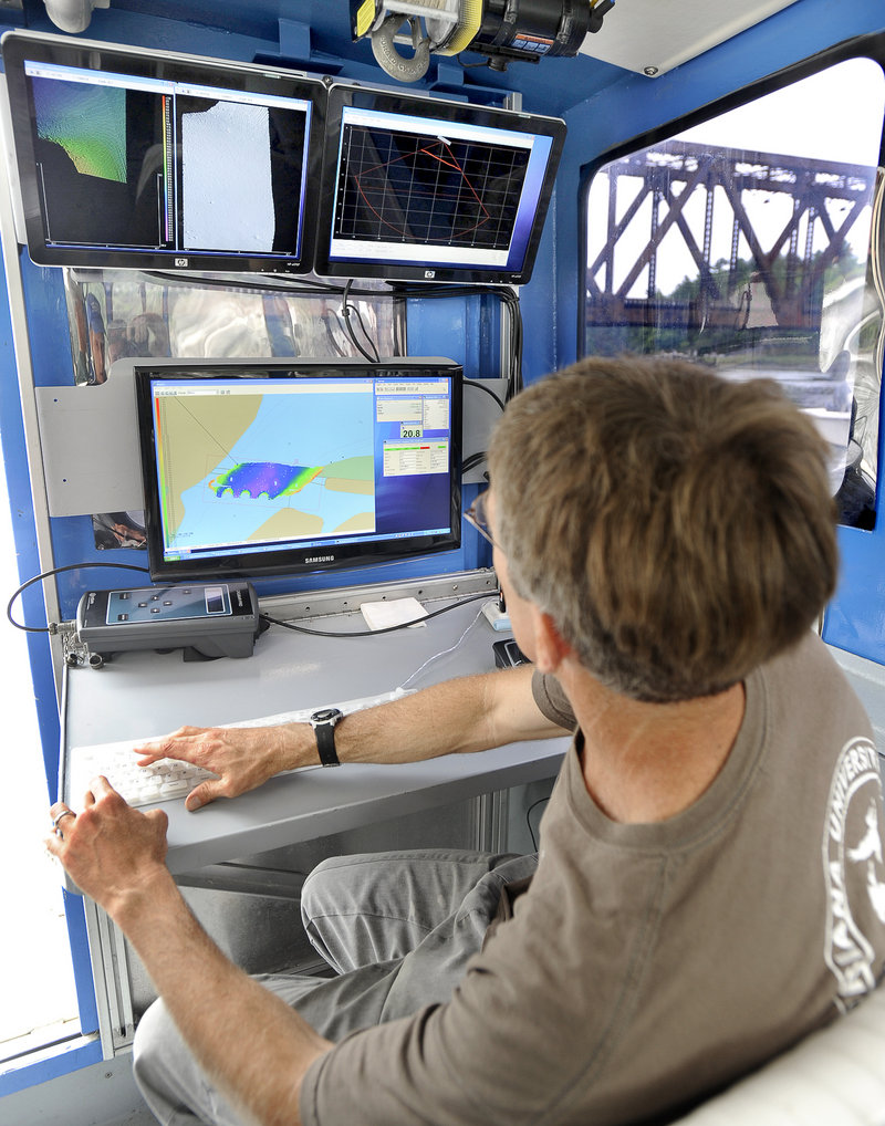 Tom Waddington, chief hydrographer for Substructure Inc. of Portsmouth, N.H., monitors data aboard the Orion, a custom-designed 31-foot aluminum boat, during an underwater survey of the old Sheepscot River railroad bridge in Wiscasset last week.