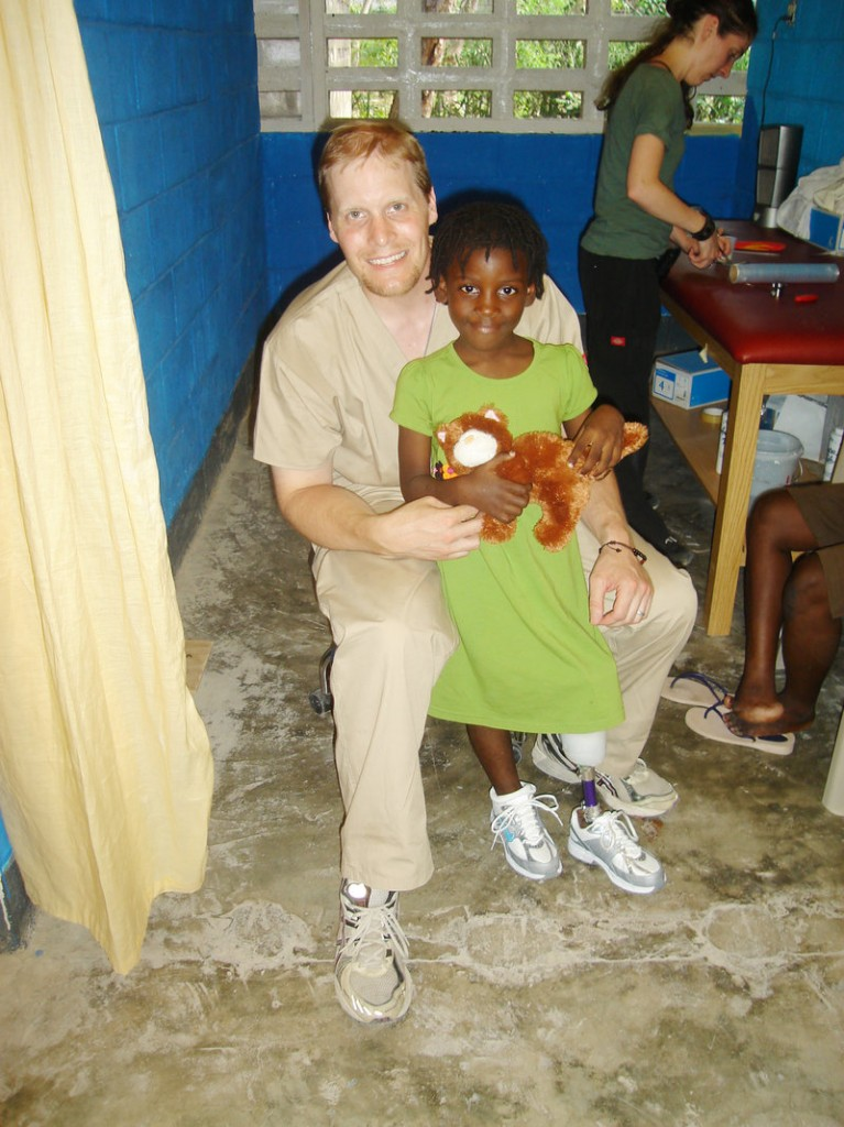 Chris Blades, a prosthetist from Portland who recently spent two weeks in Haiti, poses with a girl he helped fit with a prosthetic leg.
