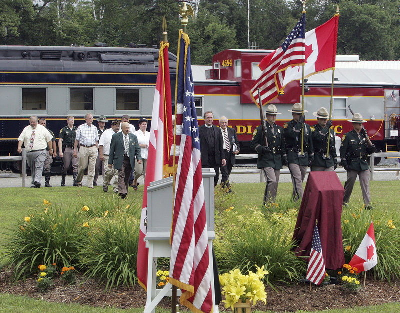 Dignitaries from the United States and Canada follow a New Hampshire state police color guard at a ceremony Friday dedicating a memorial garden to railroad workers from both countries who served in the armed forces and merchant marine.
