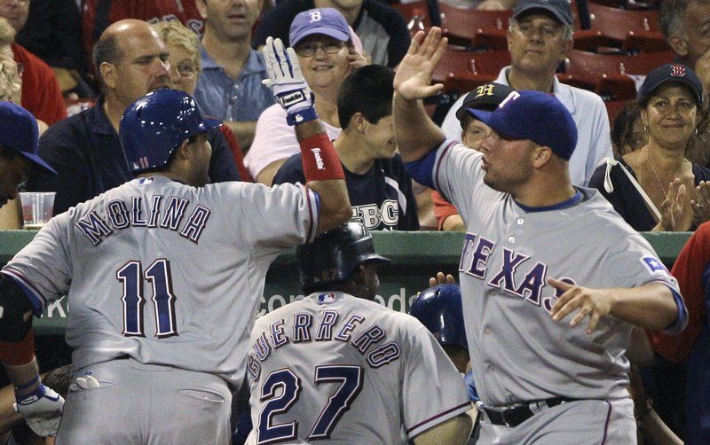 Texas' Bengie Molina, left, is congratulated by starting pitcher Colby Lewis after Molina hit a grand slam off Fernando Cabrera in a five-run fifth inning.