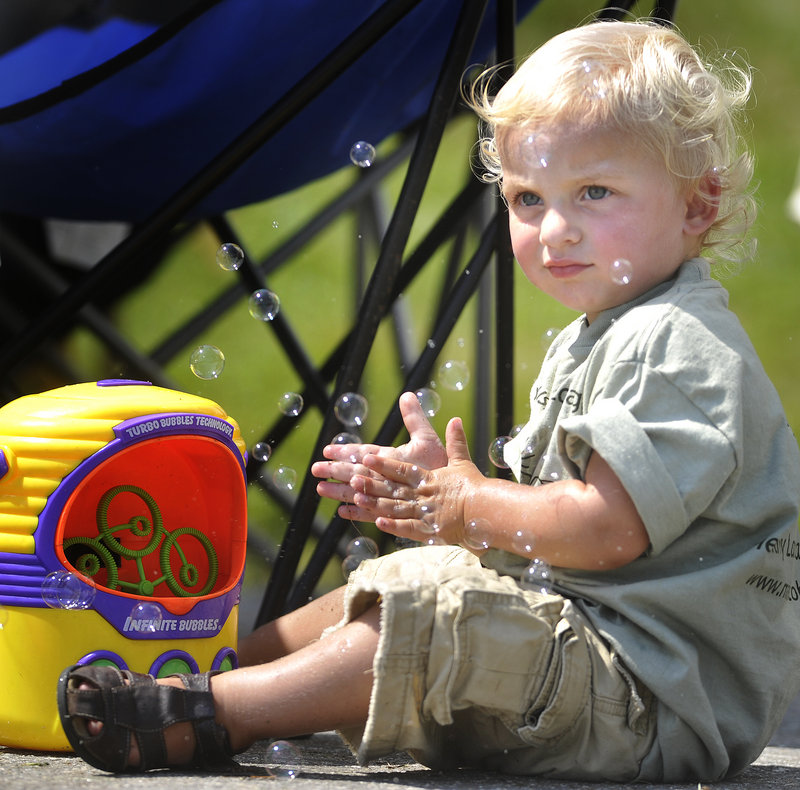 Two-year-old Sorrel Pierson of Belfast plays with a bubble-making toy at the festival on Saturday morning.