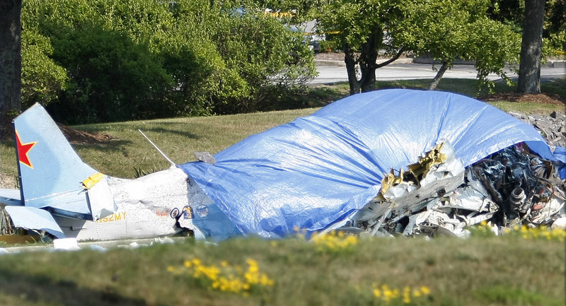 A tarp covers the remains of a Yak-52 training aircraft that crashed Saturday near the Portland International Jetport.