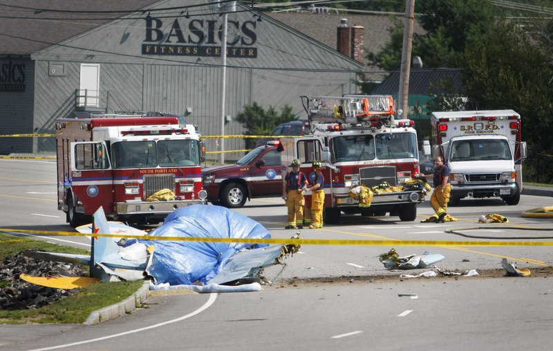 Debris from a crashed Yak-52 training aircraft litters Western Avenue in South Portland on Saturday across from Staples plaza. Two people aboard the plane, one from Brunswick and the other from Portland, were killed in the crash.