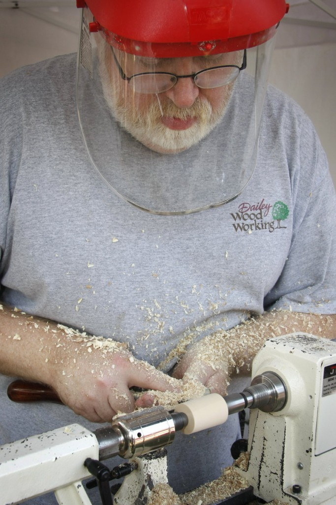 Craftsman Kim Dailey of Dailey Woodworking creates a bottle stopper with wood from Herbie, the famous Yarmouth elm tree, at the Yarmouth Clam Festival on Saturday.