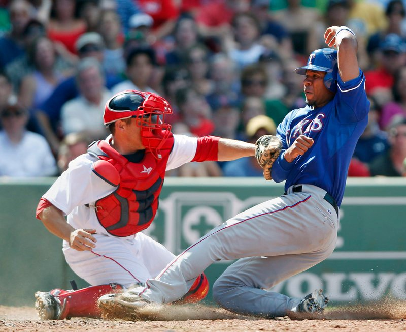 Elvis Andrus gets his foot on the plate as Red Sox catcher Kevin Cash applies the tag in the eighth inning Sunday at Fenway Park. Andrus was called safe, and the Rangers went on to a 4-2 victory.