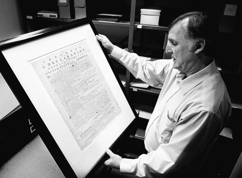Archivist Jeff Brown examines one of Maine's copies of the Declaration of Independence made in 1776.